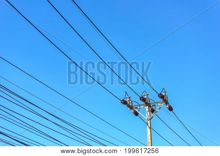 Electric pole and wires on blue sky