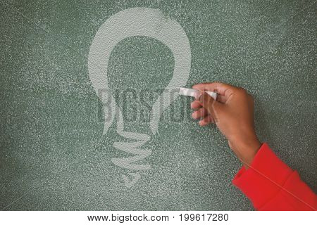 Digital composite image of yellow light bulb against hand writing on chalk board