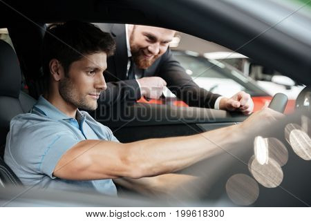 Young man testing a new car with a salesperson at the dealership