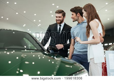 Handsome young car salesman telling a young couple about the features of the car at the dealership