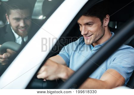 Young smiling couple testing a new car while sitting inside with a dealer