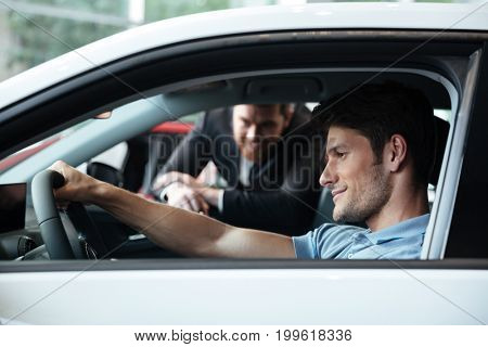 Young man testing his new car at the dealership