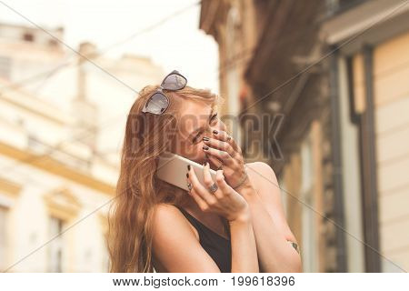 Modern attractive girl talking on her cellphone outdoors.
