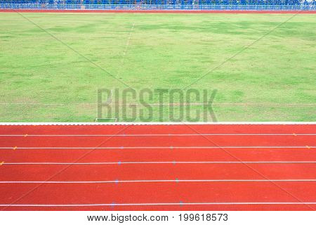 Red running track in stadium with field grass