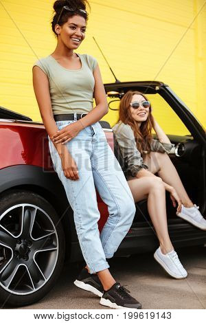 Photo of happy two young women friends standing near car over yellow wall.