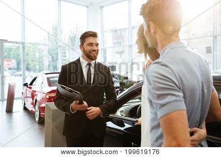 Smiling salesman showing new car to a couple in showroom salon poster