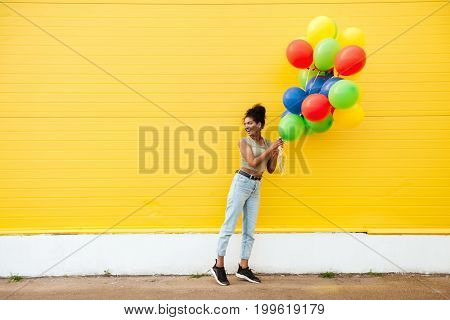 Image of young happy african woman standing over yellow wall. Have fun with balloons.