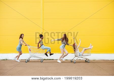 Image of young smiling women friends over yellow wall. Have fun with shopping trolley.