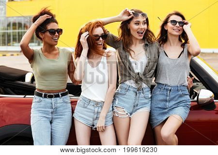 Four excited pretty girls in summer clothes leaning on a car and looking away at someone outdoors