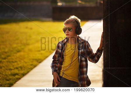 Handsome teenage boy in plaid shirt listening to music and using phone on sunset