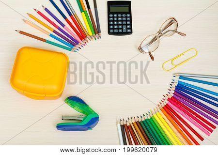 School Supplies. Color Pencils, Yellow Sandwich Box, Calculator, Glasses, Big Paper Clip And Stapler