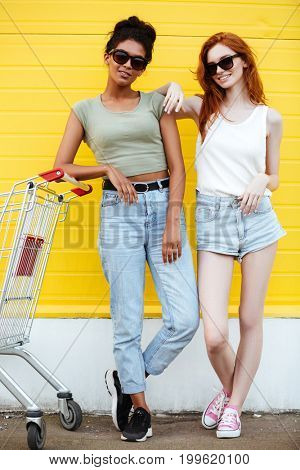 Image of two young happy ladies friends standing over yellow wall. Looking at camera.
