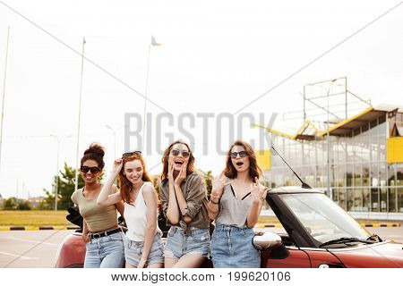 Image of happy four young women friends standing near car outdoors.