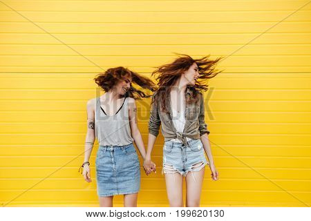 Picture of two young smiling women friends standing over yellow wall shaking hair.