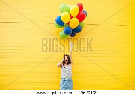 Image of young shocked woman standing over yellow wall. Have fun with balloons.