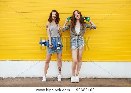Image of two young happy women friends standing over yellow wall. Looking at camera holding skateboards.