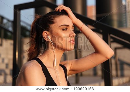 Picture of concentrated serious young sports woman sitting with earphones outdoors and looking aside.