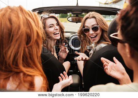 Image of smiling emotional four young women friends sitting in car outdoors talking.