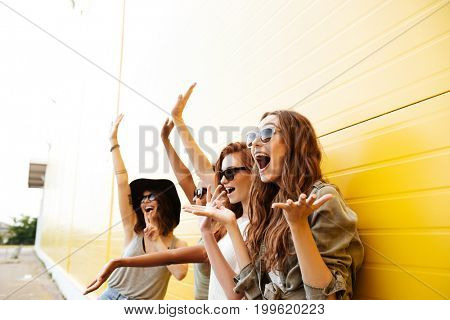 Picture of four young happy women friends standing over yellow wall. Looking aside. and waving
