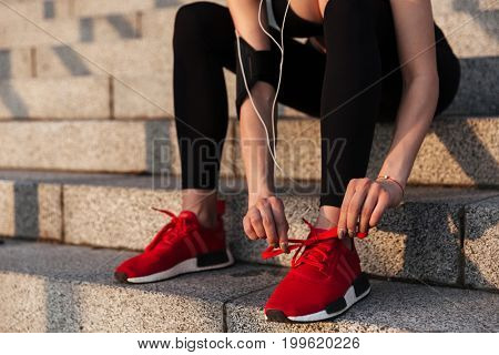 Cropped image of young sports lady sitting with earphones outdoors and tie laces.