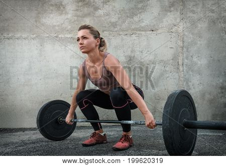 The girl lifts the barbell at a training session near the concrete wall