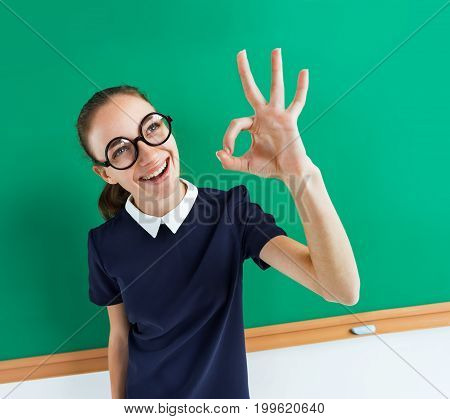Happy young student showing okay gesture. Photo of teen near blackboard education concept
