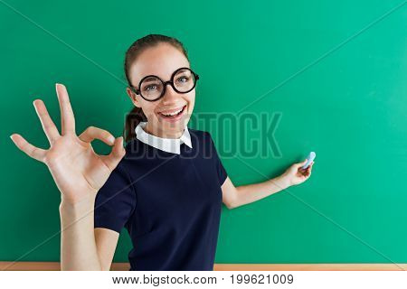Smiling student shows gesture okay and points to something. Photo of teen near blackboard education concept