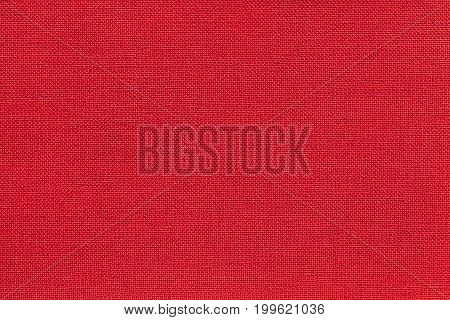 Dark bright red background from a textile material with wicker pattern closeup. Structure of the ruby fabric with natural texture. Cloth backdrop.