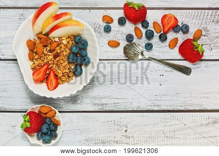 Nutritious breakfast of multigrain muesli fresh organic fruits - strawberry blueberry apple and almond nuts. Healthy dieting concept top view.