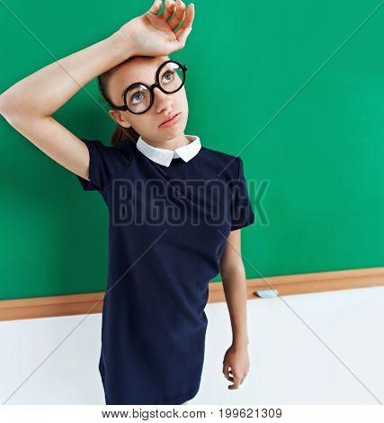 Tired student near the blackboard. Photo of a smart student in uniform education concept. Copy space for your text