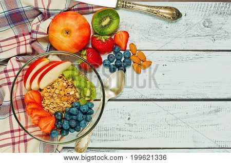 Healthy breakfast concept - multigrain granola with apple kiwi almonds strawberry and blueberry - top view in rural style on wooden table with vintage knife and checkered textile
