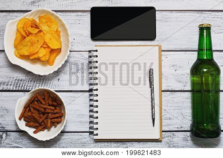 Bottle of beer potato chips and salted crackers smartphone and diary - flat lay on the wooden table. Summarizing the day concept.