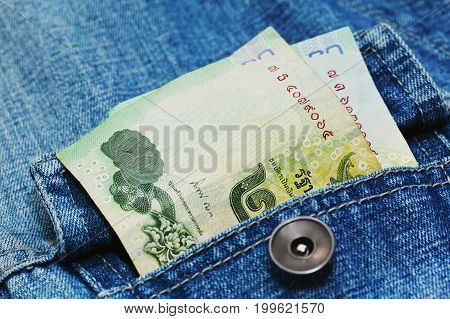 Two Thailand banknotes of 20 thai baht - around 11 USD - in jeans pocket. Close up capture poverty concept.