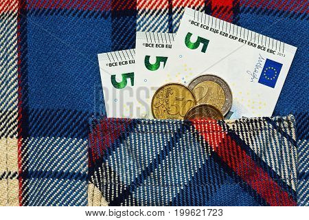 Some euro money - banknotes and coins - in work checkered shirt pocket. Symbol of low salary poverty concept.