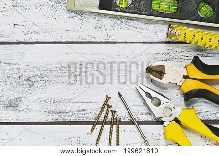 Workshop concept with variety of different hand tools on rough wooden background. Pliers nippers screwdriver screws level and ruler. Top view capture.