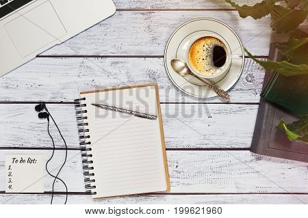 Freelance blogger journalist or writer workspace concept. Laptop books sketchbook with pen earphones to do list and a cup of coffee. Top view in rustic loft style.