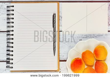 Freelancer workspace concept. Flat lay with blank diary note reminder and apricots in a bowl on rustic wooden table in retro style