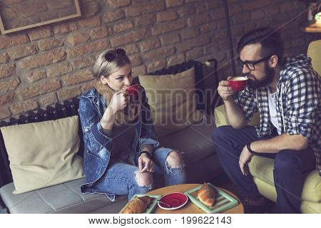 Two people sitting in a cafe having breakfast drinking coffee and enjoying a time spent with each other. Focus on the girl