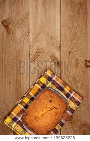 Freshly baked homemade cake on wooden background top view