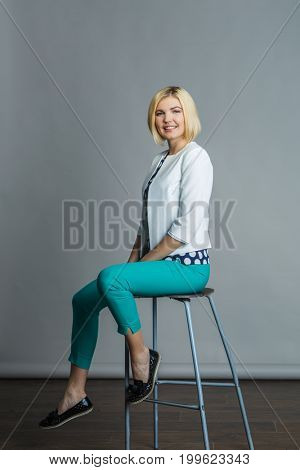 Model sitting on bar chair
