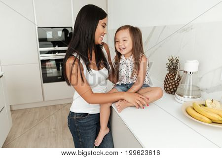 Smiling asian woman cooking with her little daughter together in a kitchen at home