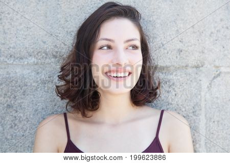 Laughing caucasian woman with long dark hair looking sideways outdoor in the summer