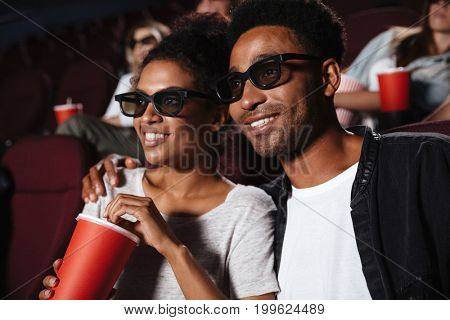 Smiling attractive afro american couple watching 3D movie and eating popcorn while sitting in a movie theater