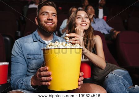Happy smiling couple holding a big popcorn bucket while watching a movie at the cinema