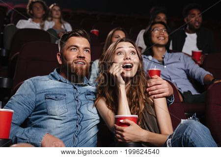 Surprised young couple sitting at the cinema and watching the movie