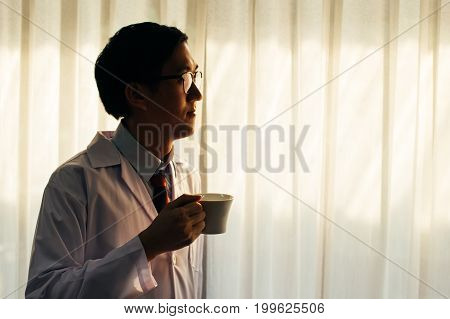 Smart Doctor In Gown Holding A Cup Thinking In The Hospital Near Window