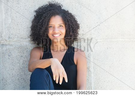 Beautiful african american woman with curly black hair outdoor in the summer