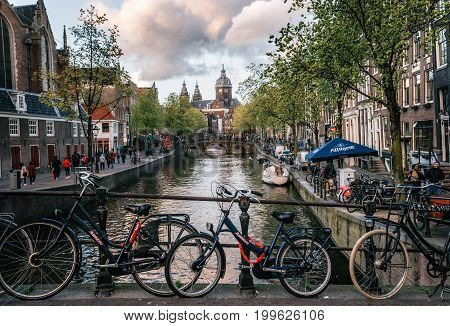 Amsterdam Netherlands - 25 April 2017: Bicycles parked along the bridge. Red-light district De Wallen View of Basilica of Saint Nicholas in the evening canal of Amsterdam Holland Netherlands.