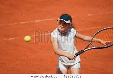 Junior Tennis Player About To Hit The Ball During Game