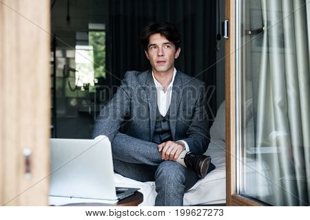 Successful businessman working with laptop while sitting on a bed in a hotel room